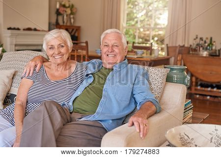 Happy portrait of a relaxed senior man with his arm around his wife's shoulder sitting content together on their living room sofa at home