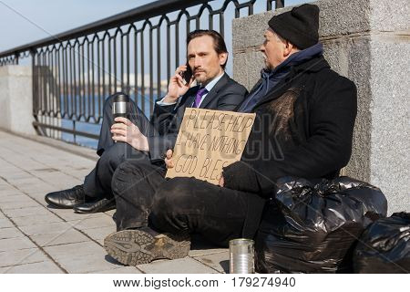 Want to wash. Serious bearded man keeping thermos with hot tea sitting on the pavement while looking sideways