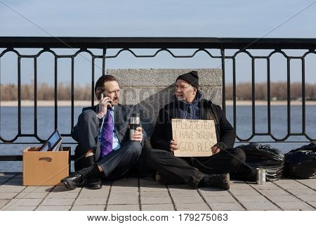Need higher salary. Serious man holding thermos with hot tea sitting on the pavement while looking sideways