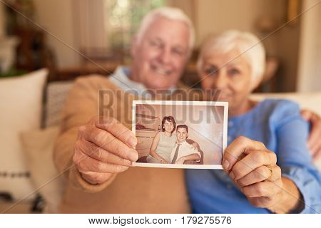 Portrait of a senior couple holding up an old photograph of themselves when they were young while sitting on their living room sofa at home