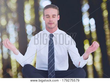 Digital composite of Man Meditating peaceful in woods