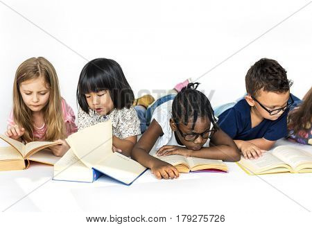Group of cute and adorable children lay down wtih textbook