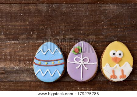 a pile of some different handmade cookies patterned as decorated easter eggs and as a funny chick against a rustic wooden background, with a blank space