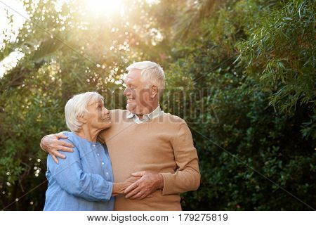 Smiling senior couple looking at each other while standing in each other's arms together outside in their backyard on a sunny day