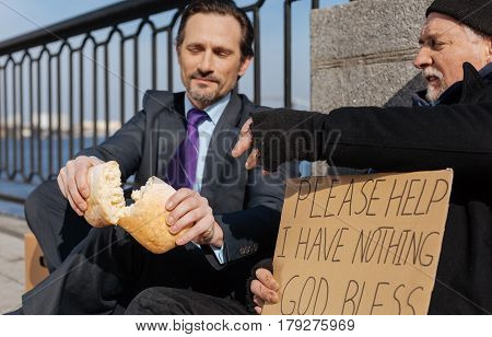Having hunger. Homeless man holding cardboard in right hand while stretching his left hand to bread sitting in semi position