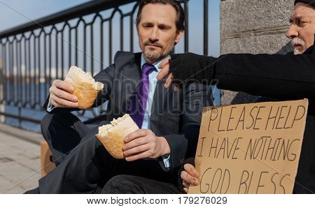 Refresh yourself. Poor homeless man holding cardboard in right hand while stretching his left hand to bread leaning on the column