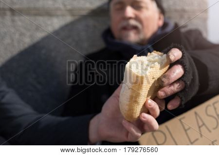 It is for you. Poor hungry man taking piece of bread with dirty hand keeping mouth opened while leaning on the wall