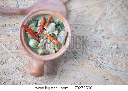 Green curry with pork (Kang Keaw Wan) on wooden background top view Thai local food