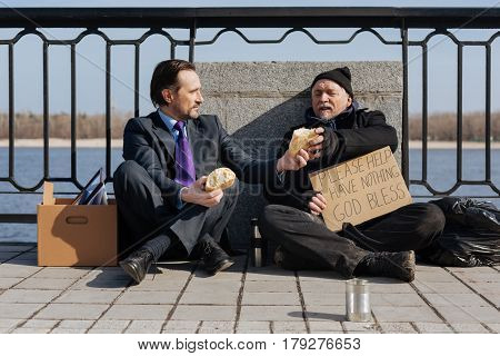 Enjoy it. Cheerful office worker sitting between his stuff and homeless man crossing legs, sharing one loaf of bread