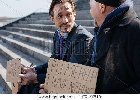 True friend. Young man wrinkling his forehead keeping smile on his face while holding cardboard with notes