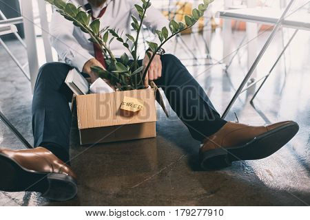 Cropped Shot Of Young Fired Businessman Sitting On Floor With Belongings In Box