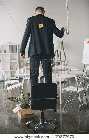 Back View Of Fired Businessman Standing On Chair And Trying To Hang Himself In Office