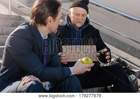 Take some vitamins. Serious brunette wearing smart costume keeping left hand on the right knee while looking at poor man