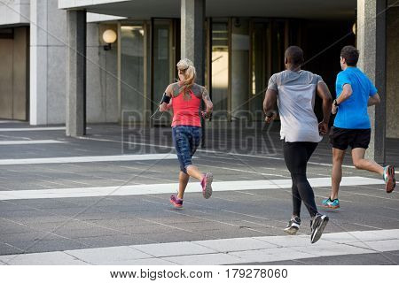 Group of runners sprinting in the city, towards their end goal accomplishment workout