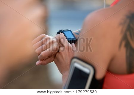 Anonymous woman with tattoos looking at her run exercise progress with wearable technology device in urban city
