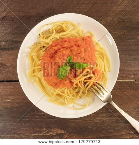 A square overhead photo of a plate of spaghetti with a fresh homemade tomato sauce, and a place for text