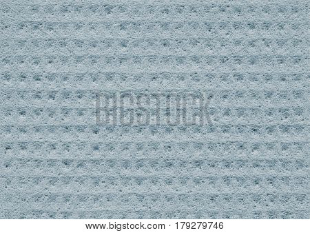Light blue texture of porous spongy material close-up. Abstract fabric background for design