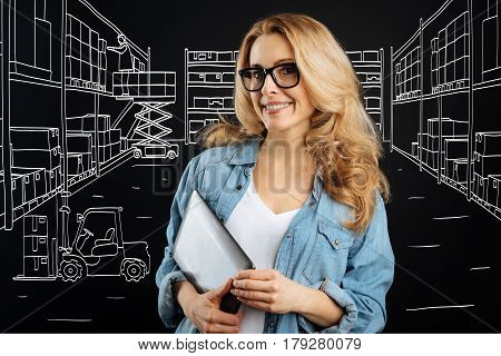 Delivery department. Pleasant delighted intelligent woman holding a tablet and smiling while working at the delivery department of the post office
