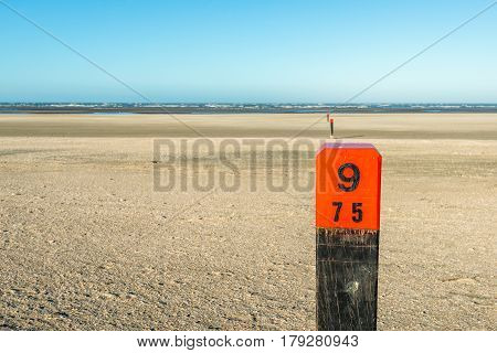Closeup of a hardwood pole with an orange head and a painted mark on an empty beach at the Dutch North Sea. It is a sunny and very windy day in the autumn season.