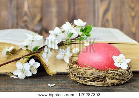 Easter card with Easter egg in the nest spring flowers and old book in background