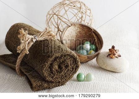 Rolled towel and balls for massage on a light woven napkin preparation for a spa procedure