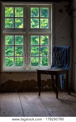 The old and wooden chair in a room.