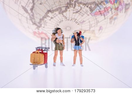 Close Up Of Miniature Backpacker And Tourist People With Earth In Background For Travel Concept