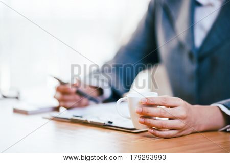 A businesswoman drink coffee while working in office