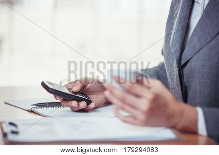 Businesswoman surf internet on smartphone and holding coffee cub