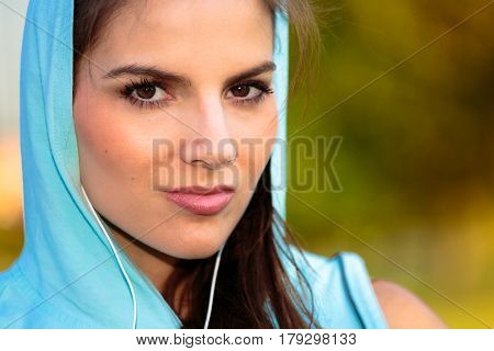 Woman With Hooded Listening To Music From Her Smart Phone