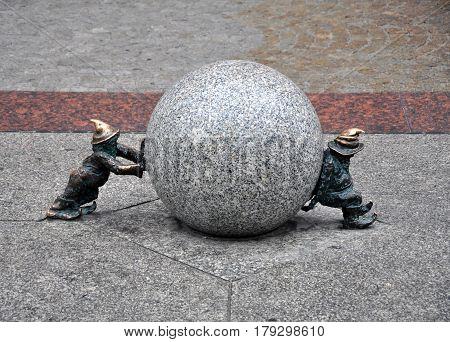Wroclaw, Poland - October 13, 2016: Metal sculpture of dwarfs rolling a granite ball. Wroclaw Street, Lower Silesia.