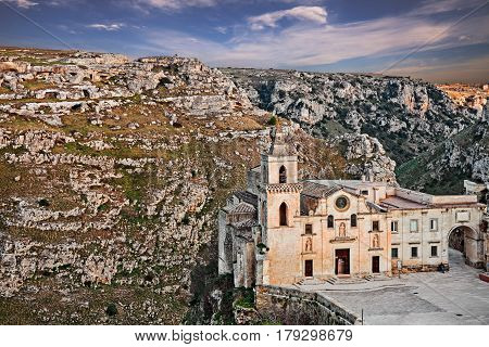 Matera, Basilicata, Italy: landscape at sunset of the old town (sassi di Matera) with the church of Saints Peter and Paul (know also as San Pietro Caveoso) and the deep ravine with the old cave houses