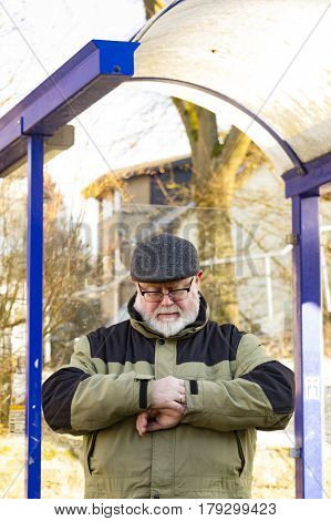 Male senior is waiting on Bus Stop in Winter