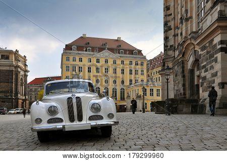 Dresden, Germany - April 12, 2016: White retro car in the historic street of Dresden, Saxony.