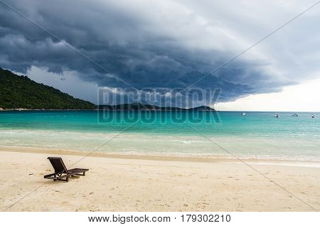 Lonely chaise longue on a deserted beach against a background of approaching thunderstorm. Thunderclouds. Pulau Perhentian Malaysia.