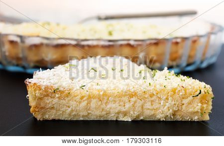 Lemon, lime, coconut impossible pie with white chocolate shavings slice with baking dish in the background