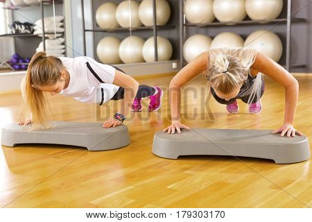 Full length portrait of confident female friends doing pushups in gym