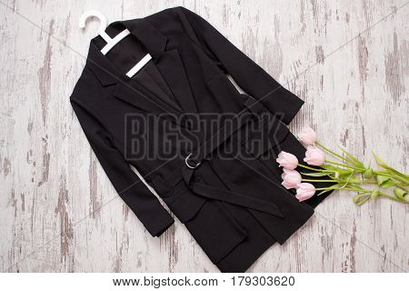 Fashion concept. Black coat hanger and pink tulips. Top view light wood background