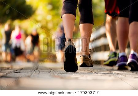Close up of the legs of woman running on the wooden walkway in the park