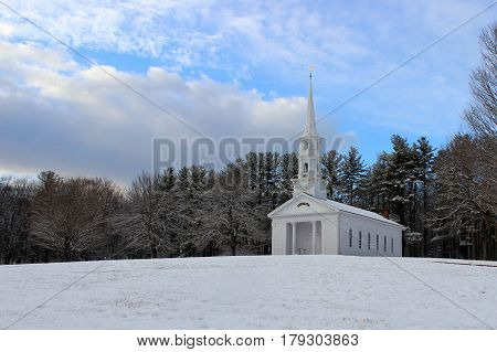 A white New England clapboard chapel on a winter day.