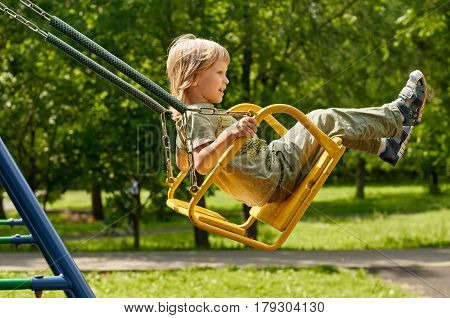 blonde boy having fun at the playground. Child kid playing on a swing outdoor. Happy active childhood.