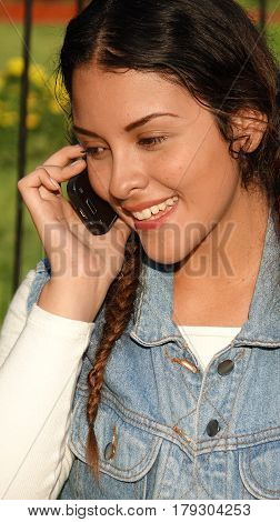 Girl With Cell Phone Wearing a Jean Jacket
