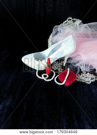 Composition made of white women's shoes with high heels, red lipstick and pink dress. Fashion concept. Glamorous composition for a wedding, a prom and a date
