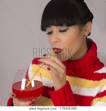 The young woman is drinking red drink with straw in red sweater on gray background.