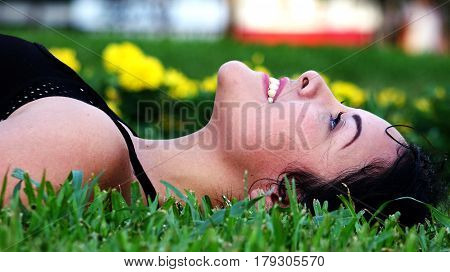 teen girl daydreaming and laying in the grass
