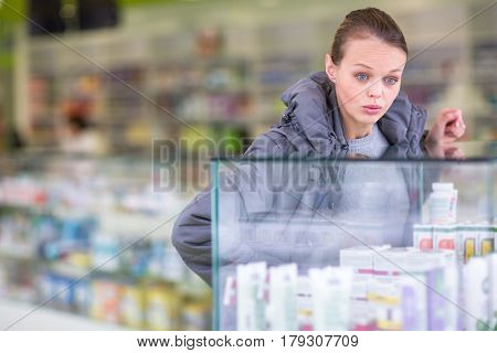 Young woman looking for the right pills in a modern pharmacy - surprised by the prices of these pharamceuticals (shallow DOF; color toned image)
