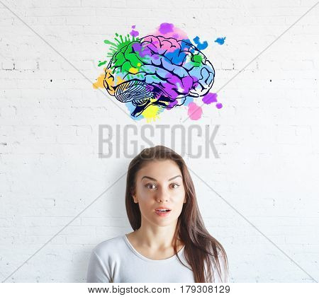 Surprised young woman on white brick background with colorful brain sketch. Creative mind concept