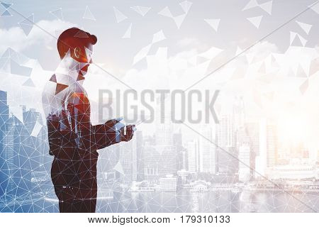 Side view of handsome man with document in hands on abstract city background with polygonal pattern. Double exposure