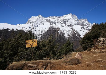 Directional sign and snow capped mountain. Scene near Namche Bazar Everest National Park.