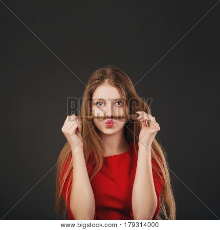 Beautiful Teenage Girl Making Funny Faces Using Her Long Blonde Hair To Make Mustaches.